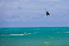 Male Kitesurfer grabing his board Stock Photo