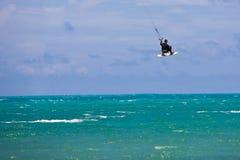 Male Kitesurfer grabing his board Stock Photo