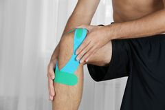 Male knee with applied physio tape, indoors. Male knee with applied physio tape indoors royalty free stock photo