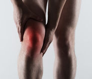 Male knee pain. Acute pain of male leg shown with red spot. Bone fracture, emergency concept Royalty Free Stock Photo