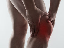 Male knee pain. Red spot on painful male knee over light grey background. Man having rheumatism and sprain problem royalty free stock images