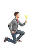 A male kneeling and holding a flower Stock Photo