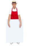 Male kock som presenterar dig det blanka annonserande brädet Arkivbilder