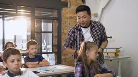 Male Korean teacher of elementary school walking between desks puts digital tablets on desk while group of. Schoolchildren sitting at the desks at classroom stock video footage