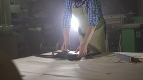 Male kraftman with beard in a workshop with a sample of leather for making furniture. Male kraftman with a beard in a dark workshop with a sample of leather for stock video footage