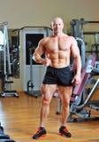 Male kroppsbyggare som visar tum upp i idrottshall Fotografering för Bildbyråer