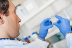 Male lab technician holding a test tube with sample Stock Photo