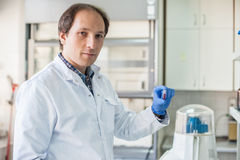 Male lab technician holding a test tube with sample Royalty Free Stock Photos