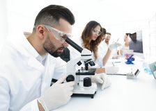 Male lab technician looks at the sample under a microscope. Sitting at Desk in lab Royalty Free Stock Image