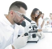 Male lab technician looks at the sample under a microscope. Sitting at Desk in lab Stock Photography