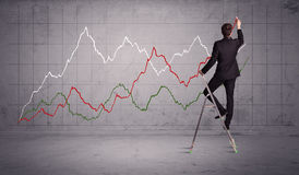 Male on ladder drawing chart lines Stock Photos