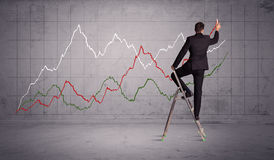 Male on ladder drawing chart lines Stock Image