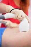 Male laser epilation. Man receiving laser epilation at armpit on beauty center Stock Image