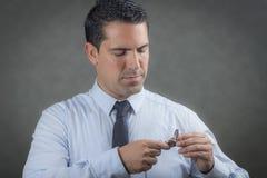 Male latin holding his pocket watch. Latino man holding his pocket watch Royalty Free Stock Images