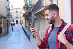 Male laughing while texting outdoors with copy space.  Royalty Free Stock Photos