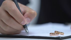 Male lawyer filling data in documents, engagement rings on table, family court. Stock footage stock video