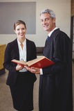 Male lawyer holding book while standing with female colleague. Portrait of happy male lawyer holding book while standing with female colleague in office Stock Image