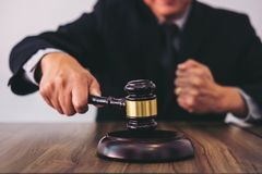 Male lawyer or judge hand`s striking the gavel on sounding block Royalty Free Stock Photo