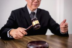 Male lawyer or judge hand`s striking the gavel on sounding block Stock Images