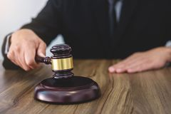 Male lawyer or judge hand`s striking the gavel on sounding block Royalty Free Stock Images