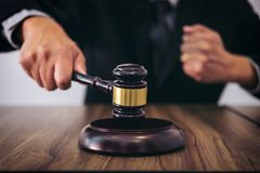 Male lawyer or judge hand`s striking the gavel on sounding block Stock Image