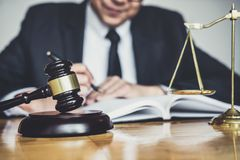 Male lawyer or judge working with contract papers, Law books and wooden gavel on table in courtroom, Justice lawyers at law firm,. Law and Legal services stock photos