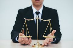 Male lawyer in the office with brass scale. Justice and law concept.Male lawyer in the office with brass scale stock photo