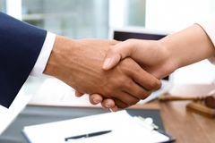 Male lawyer shaking hands with woman over table. Closeup stock images