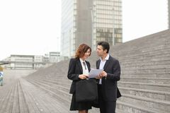 Male lawyer speaking with female client. Layer and client standing on big gray stairs. Woman hold documents about court statement in hand. Man tell about very stock image