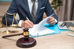 Male lawyer working with contract papers and wooden gavel on tabel in courtroom. justice and law ,attorney, court judge, concept stock photography