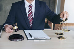Male lawyer working with gavel and scales of justice, note paper Stock Photo