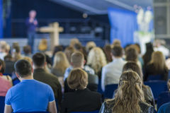 Male Leader Lecturer Speaking In front of the Large Group of People. Royalty Free Stock Images