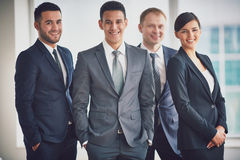 Male leader. Portrait of confident business partners looking at camera with male leader in front royalty free stock image