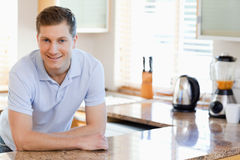 Male leaning against the kitchen counter. Smiling male leaning against the kitchen counter Royalty Free Stock Photo