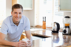 Male leaning against the kitchen counter Stock Images