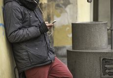 Man leaning against a wall, talking on his mobile phone. Male leaning against a yellow wall, while talking on his phone, wearing earplugs. Male wearing grey Royalty Free Stock Photo