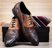 Male leather executive shoes with tie. Male shoes and tie in wooden background Royalty Free Stock Photography
