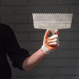 Male left arm holding large putty knife on wide abstract linear patterned textured brick wall background. Stock Photo