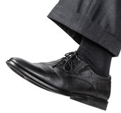 Male left foot in black shoe takes a step Royalty Free Stock Images