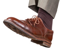 Male left foot in brown shoe takes a step Royalty Free Stock Image