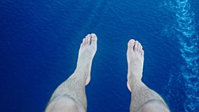 Male legs against the background of sea water on a sunny day.  Royalty Free Stock Photos