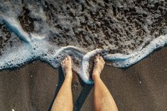 Selfie of man bare feet on sand beach and wave, summer concept. Male legs on the beach sand of the sea in summer on vacation Stock Photo