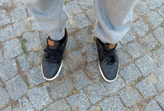 Male legs in black leather sneakers close up. Top view Royalty Free Stock Photos