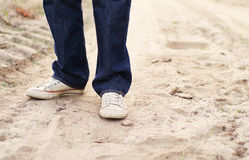 Male legs in blue jeans and gym shoes on the sandy dusty road Royalty Free Stock Photos