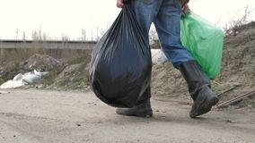 Male legs in boots walking at garbage dump. Close-up back view of male legs in dirty boots walking at garbage dump site. Man holding trash bags full of plastic stock footage
