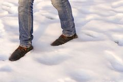 Male legs in brown boots and blue jeans are going on the snow. Copy space. Wirst step after snow catastrophe. stock photos