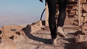 Male legs climbing up on desert stairs. Slow motion. Man steps on desert rocky hill. Back view. Stepping up. Career path. Male legs climbing up on desert stairs stock video
