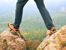 Male legs in dark hiking trousers and leather trekking shoes on peak of rock above  misty valley. Outline of hill Royalty Free Stock Photos