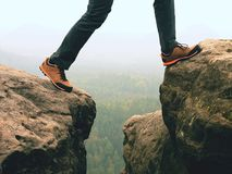 Male legs in dark hiking trousers and leather trekking shoes on peak of rock above  misty valley. Outline of hill Royalty Free Stock Image