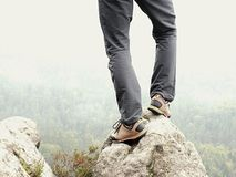Male legs in dark hiking trousers and leather trekking shoes on peak of rock above  misty valley. Outline of hill Stock Photo